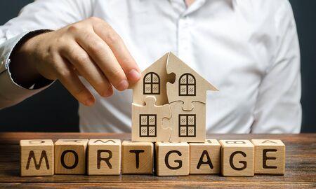 Ein Mann sammelt ein Hausrätsel über der Aufschrift Hypothek. Bau eines eigenen Wohnhauses. Hauskauf auf Kredit, Verbesserung der Lebensbedingungen. Eine Familie gründen.