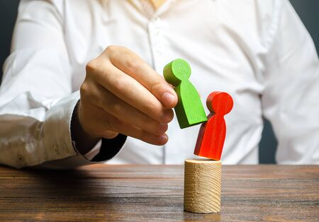 A person replaces a red human figure with a green one. firing staff. Head Offset. Business optimization, replacement of key employees with loyal ones. Change of power. Anti corruption. system recovery Stock Photo