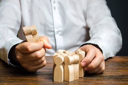 A man grabs a figurine of people from the crowd. Hiring employees. Market Segmentation and Niche Conquest. Human resources. Enticement of workers and customers from a competitor. predatory competition