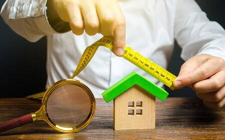 A man measures and evaluates a house. Fair value of real estate and housing. Property valuation. Home appraisal. Legal deal. Apartment purchase sale. Creating and designing a building project.