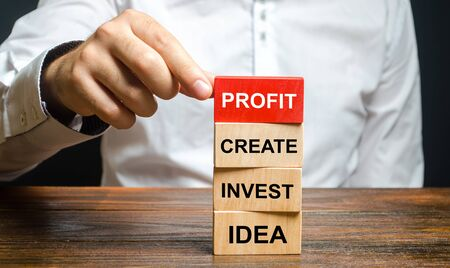 A man is building a business plan from blocks. Planning and implementation of the idea, search for investment and work, achieving the goal and making a profit. Project management. Entrepreneur