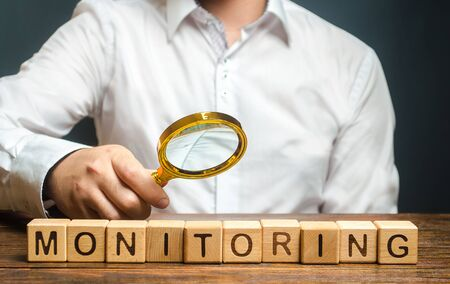A man with a magnifying glass examines word Monitoring. Verification and control, business audit. Inspector controls the quality of products or work performance. Productivity enhancement, coordination