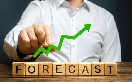 Man holds green arrow up over word Forecast. Prediction of profit growth, value of assets and market conditions. Increase income and earnings. A budget surplus, prosperous economy or company.
