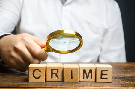Man with a magnifying glass examines the word Crime. Investigation. Collection evidence, identification of perpetrators, familiarization with court case. Detective, criminal forensic expert. Expertise