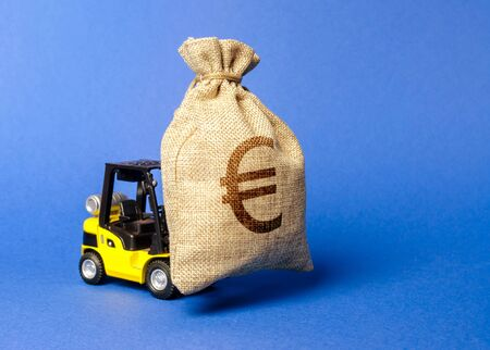 Yellow forklift truck carries a bag of euro money. Attracting investment in development, modernization of production and business. capital migration. Revenue, profit, liquidity. Stok Fotoğraf