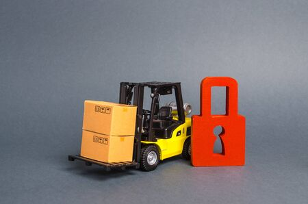 Forklift truck carries a cardboard box next to red padlock. Embargo, trade wars. No delivery. Restriction on the importation of goods, proprietary for business. Inability to sell products, ban import