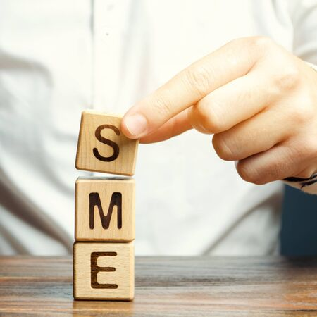 Businessman holds wooden blocks with the word SME. Small and medium-sized enterprises - commercial enterprises that do not exceed certain indicators. Stock fotó