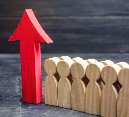 Geschäftsteam und roter Pfeil nach oben in der Nähe der Mitarbeiter. Das Konzept eines Startups. Erfolgreiches Geschäftswachstum. Qualifizierung und Umschulung der Arbeitnehmer. Starten eines neuen Projekts. Förderung. Zielerreichung Standard-Bild