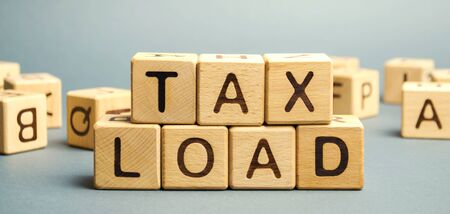 Wooden blocks with the word Tax load and randomly scattered cubes. Measure of the tax burden imposed by government. Taxation. Taxes. Business and finance concept.