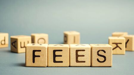 Holzklötze mit dem Wort Gebühren und zufällig verstreuten Würfeln. Festpreis für eine bestimmte Leistung. Geschäfts- und Finanzkonzept. Kosten, Gebühren, Provisionen, Strafen. Kosten, Gebühren und Steuern.