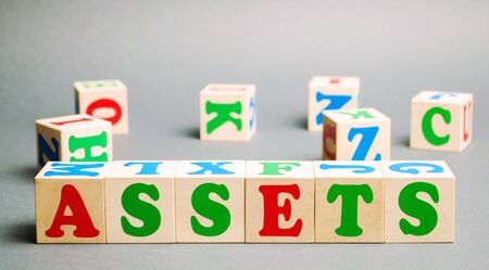 Wooden blocks with the word Assets and randomly scattered cubes. Resource owned by the business. Financial accounting. Money and finance. Cash equivalents, certificates of deposit