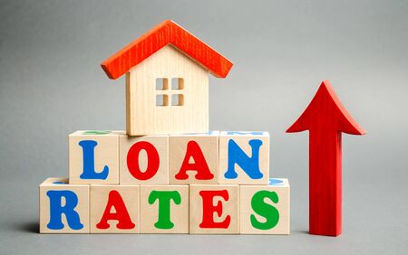 Wooden blocks with the word Loan rates, wooden house and up arrow. Mortgage and real estate concept. Expensive housing. The increase in the cost of apartments