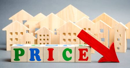Wooden blocks with the word Price, down arrow and wooden houses. The concept of low cost real estate. Lower mortgage interest rates. Falling prices for rental housing and apartments. 写真素材 - 130109002