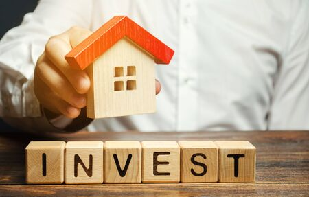 Wooden blocks with the word Invest and house in the hands of a businessman. The concept of investing in real estate construction. Effective investment. Buying apartments. Business and finance 写真素材 - 130109017