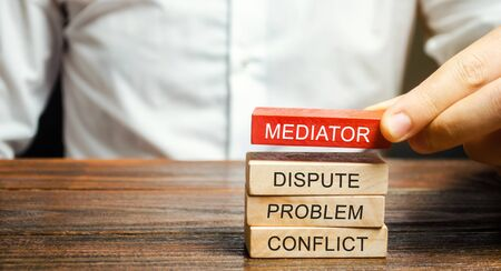 Un hombre sostiene bloques de madera con la palabra Mediador, disputa, problema, conflicto. Solución de controversias por mediador. Resolución de disputas y mediación. Tercero, intermediario.