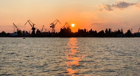 River port with ships at sunset. Busy traffic artery. Logistics and infrastructure. Loading and unloading of ships, trade traffic. Industry and economics. Plants and factories. Transport hub. Dnipro