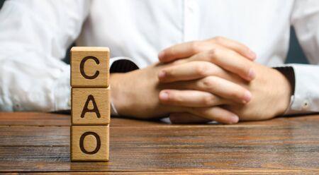Le mot CAO et un homme aux mains verrouillées. Chef de la comptabilité. Poste vacant et fonctions d'un spécialiste. Gérer les impôts et la paie. Développer et mettre à niveau les systèmes financiers dans les entreprises. cadres financiers, Banque d'images
