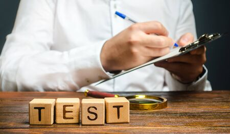 Word test and a man with a clipboard in the background. Organization, review. Pass inspection, permission for the business. Driving license. Quality control, audit. The inspector conducts a check. 스톡 콘텐츠 - 130109569