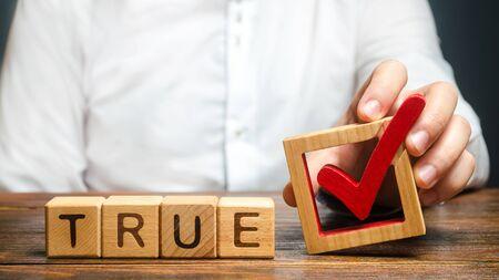 Un homme tient une coche rouge sur le mot True. Confirmez la véracité et la vérité. Lutte contre la propagande hostile aux fake news. Confirmation des faits, réfutation des rumeurs. Démystifier les mythes et les idées fausses