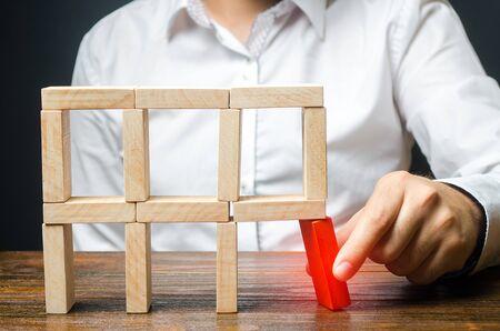 L'homme enlève l'élément structurel rouge, qui va s'effondrer. Homme d'affaires incompétent. Perte d'éléments clés et d'employés. Dommage pour l'adversaire. Destruction d'une structure complexe par négligence.
