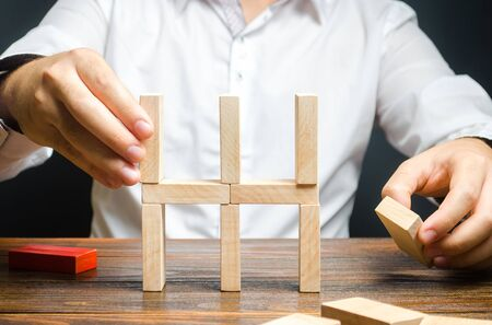 Businessman collects a house of dominoes. Conceptual creation of a new business or startup, establishing processes. Construction of a residential building. Mortgage. Real estate market and investment. Stockfoto