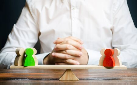 A man with hands in the gesture of a lock and looks at the red and green standoff groups on a scales. conflict resolution and the search for a compromise in the dispute. Research argument of each side
