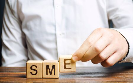 Businessman holds wooden blocks with the word SME. Small and medium-sized enterprises - commercial enterprises that do not exceed certain indicators. Stok Fotoğraf