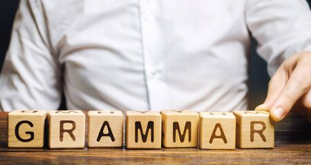A man puts wooden blocks with the word Grammar. Set of structural rules governing the composition of clauses, phrases and words in a natural language. Phonology, morphology, syntax, phonetics