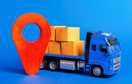 A blue truck loaded with boxes and a red pointer location. Services transportation of goods, products, logistics and infrastructure. Transportation company. Location of carriers. Package tracking