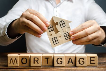 A man collects a house from the puzzles over the inscription Mortgage. Construction of your own residential building. Buying a home on credit loan, improvement of living conditions