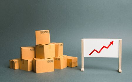 Plenty of cardboard boxes and whiteboard with red positive trend chart. Increasing consumer demand. rate growth of production of goods and products, increasing economic indicators. Trade balance
