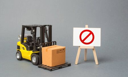 Forklift truck carries a cardboard box near a stand with a red symbol NO. No delivery. Restriction on the importation of goods, proprietary for business. Inability to sell products. trade wars. Stockfoto
