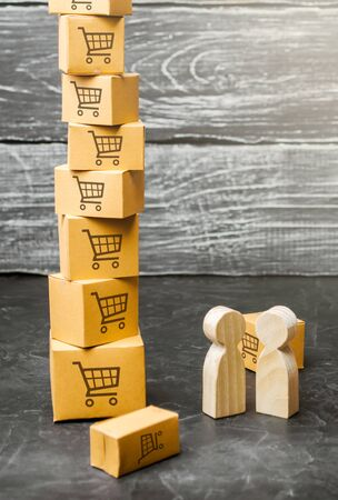 Two wooden people stand near a tower of boxes. buyer and seller, manufacturer and retailer. Discussion of the terms of the trading deal, the purchase of goods and services. Business and commerce.