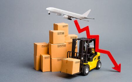 Cargo airplane, forklift truck with cardboard boxes and a red arrow down. Drop in industrial production and business. Decrease freight transportation and volumes of delivery of products and goods.