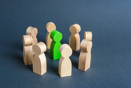 A green human figure is surrounded by a circle of people. Cooperation and collaboration. Fundraising and people around the idea. To unite like-minded persons. Leader and leadership skills. Stockfoto