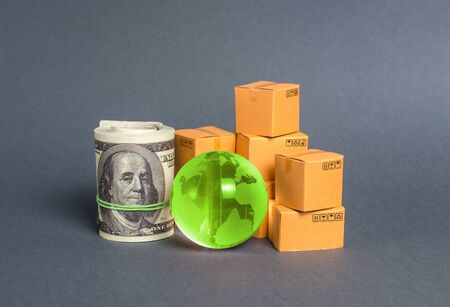 A stack of boxes, a bundle of dollars and a green planet earth globe. World trade and commodity exchange. commerce traffic trading balance. Import, export, transit of products. Economic relations.