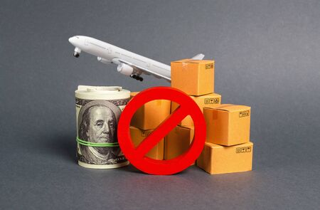 The prohibition sign NO blocks, bundle of dollars money and boxes with a airplane. Embargo, trade wars. Restriction on importation goods, proprietary for business. Sanctions and economic restrictions