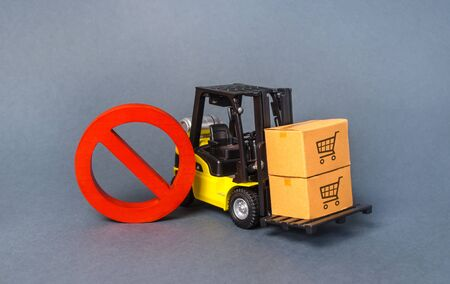 Yellow Forklift truck carries boxex and a red prohibition symbol NO. Embargo trade wars. Restriction on importation production, ban on export of dual-use goods to countries under sanctions