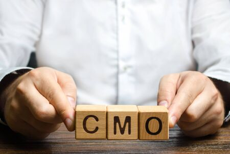 Man holds abbreviation CMO. Marketing strategy of the company. Post top manager Chief Marketing Officer. PR and advertising, establishing public relations and the media