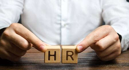 Businessman holds two blocks with HR. Recruiting new workers, headhunters Human resources. Search for talented worker. Assessment of qualities skills. Attraction of valuable personnel to the company