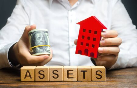 A man holds a red house and a roll of dollars over the word Assets. Declaration income and taxation, audit of ownership of real estate and cash. Reliable investment. Property tax