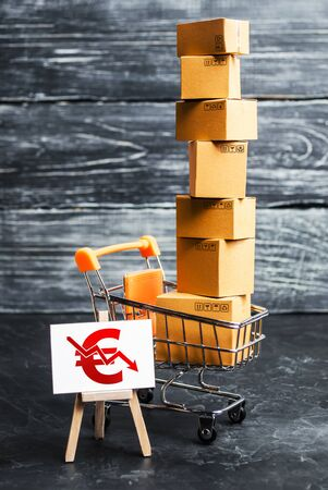 A shopping cart loaded with boxes and a sign with a euro symbol down arrow. Decrease in income from sales of goods and retail. Fall in purchasing power. Price reduction, discounts Stockfoto