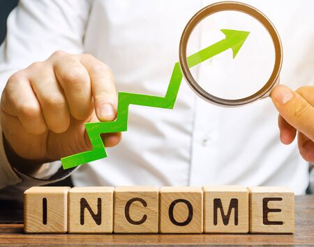 Blocs de bois avec le mot revenu et la flèche vers le haut entre les mains des hommes d'affaires. Le concept d'augmentation des profits et des finances. Évolution du budget de l'entreprise. Analyse et analyse d'affaires. Revenu
