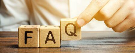 Biznesmen stawia drewniane klocki z napisem FAQ (najczęściej zadawane pytania). Zbiór najczęściej zadawanych pytań na dowolny temat i odpowiedzi na nie. Instrukcje i zasady na stronach internetowych