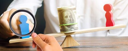 Wooden figures of man and women on the scales. Concept of gender pay gap. Income inequality. Oppression of women. Gender discrimination. Underestimation of female labor. Segregation. Stockfoto