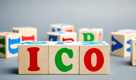 Wooden blocks with the word ICO ( Initial coin offering ). Attracting investments in the form of selling to investors a fixed number of new units of cryptocurrencies
