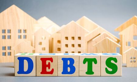 Wooden blocks with the word Debts and miniature houses. Debt concept for housing or mortgage. Real estate and credit, loan