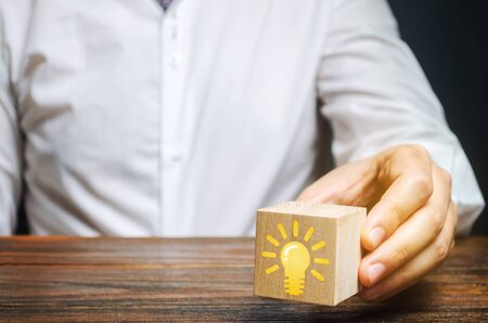 Businessman holds a wooden block with an image of a light bulb idea. Generation of innovative business ideas. Creative process. The accumulation of experience and skills.