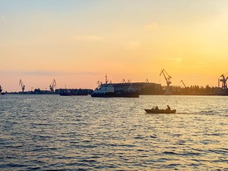 River port with ships at sunset. Busy traffic artery. Logistics and infrastructure. Loading and unloading of ships. Industry and economics. Plants and factories. Beautiful view