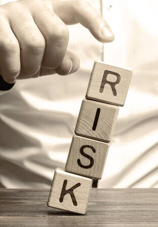 Man removes blocks with the word Risk. The concept of reducing possible risks. Insurance, stability support. Legal protection of business interests. Financial pillow. Favorable investment climate.